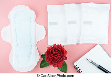 Red flowers with sanitary napkin and pen on notebook for note