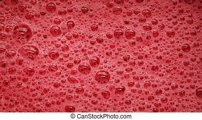 Red Foam With Bubbles Popping - Red foam bubbling closeup...