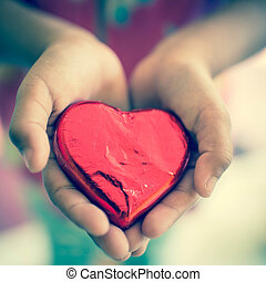 Red foil wrapped candy heart in kid's hands