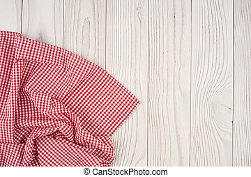 Red folded tablecloth over bleached wooden table.