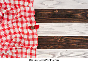 red folded tablecloth over wooden table.