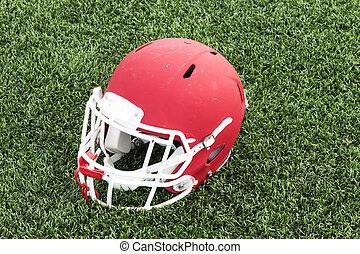 Red football helmet on a green turf field