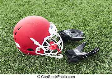 Red football helmet with balck gloves on the field