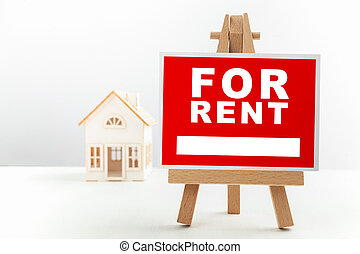 Red For Rent Real Estate Sign in Front of Small House Model.
