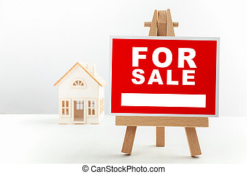 Red For Sale Real Estate Sign in Front of Small House Model.