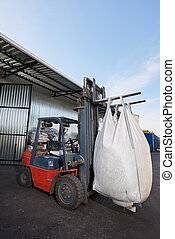 Red forklift lifts big white heavy sack