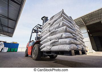 Red forklift lifts pallet with heavy bags