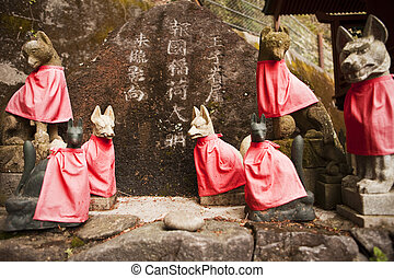 Red Fox Guardians at Shinto Shrine - Stone foxes (kitsune),...