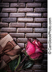 Red fragrant rose wrapped giftbox on wicker wooden matting