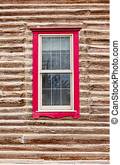 Red framed window in log house wall architecture