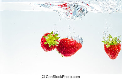 red fresh fruit strawberries falling into water with splash on white background, strawberry for health and diet, nutrition