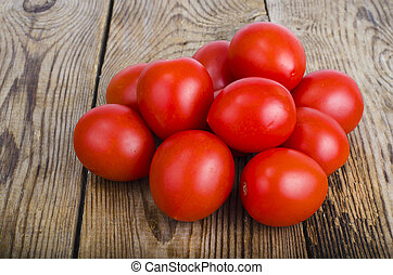 Red fresh tomatoes on wooden background