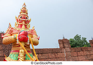 red giant statue standing front of wall and sky background