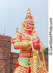 red giant statue standing front of wall