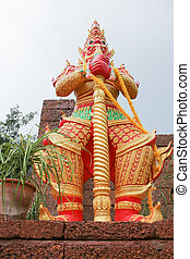 red giant statue standing with base on white sky background
