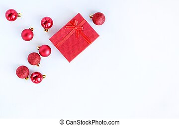 Red gift box and Christmas balls on a white background.Christmas, winter holidays, festive delivery concept. Top view, flat lay with copy space.