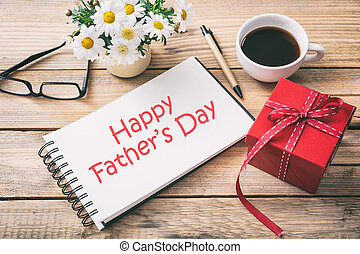 Red gift box and happy fathers' day on the notebook, office desk background