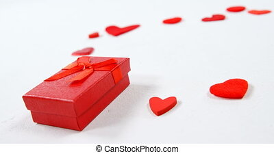 Red gift box and red hearts on white surface 4k