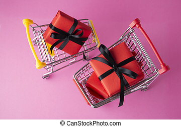 Red gift box in shopping cart on pink background