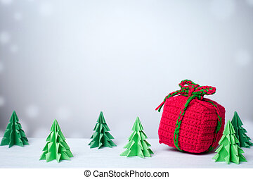 Red gift box in snowy winter background with paper cut christmas tree