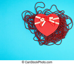 red gift box in the form of a heart with a bow on a blue background