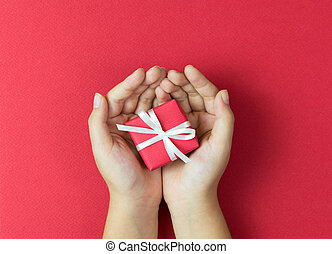 Red gift box tied with ribbon and bow in hands over red ...