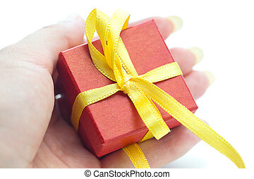 red gift box with a yellow ribbon in the hand of women
