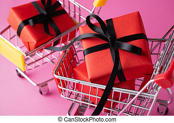 Red gift box with black bow closeup in shopping cart