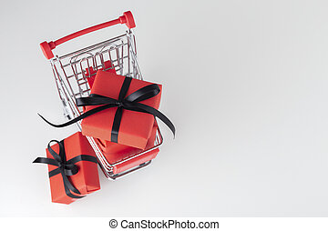 Red gift box with black bow in shopping cart, black friday background