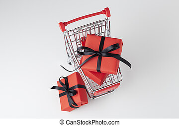 Red gift box with black bow in shopping cart