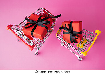 Red gift box with black bow in shopping carts