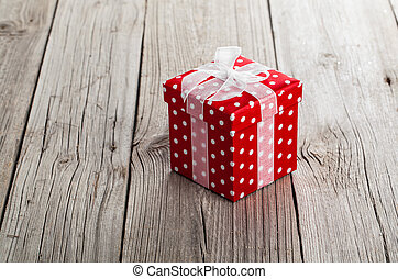 red gift box with bow on wood background