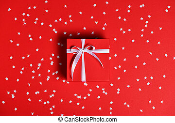 Red gift box with confetti on red background