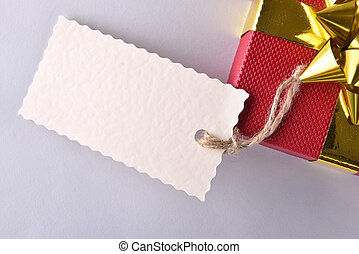 Red gift box with golden ribbon and label close up