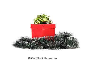 Red gift box with green-golden bow and tinsel.