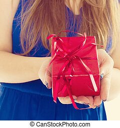 red gift box with hands of a young woman