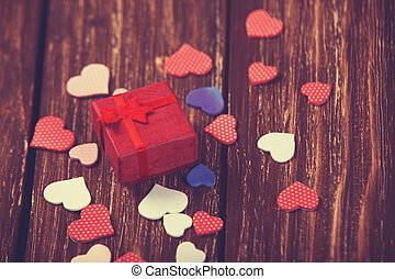 Red gift box with hearts on wooden table.