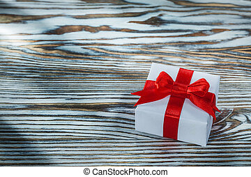 Red gift box with knot on wooden background