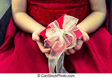red gift box with ribbon in hands