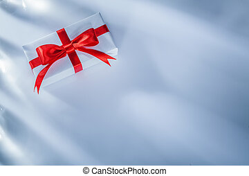 Red gift box with tied bow on white background