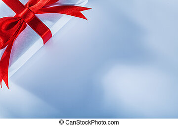 Red gift box with tied ribbon on white background