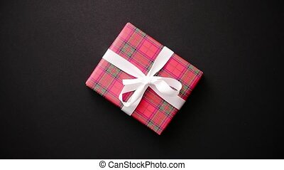 Red gift box with white bow on black table, top view - Gift...