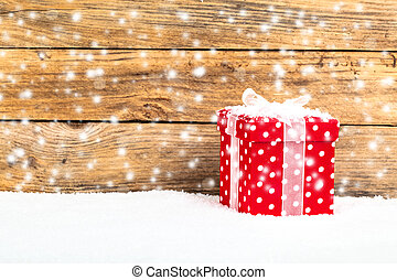 red gift for christmas on a wooden background with snow -...