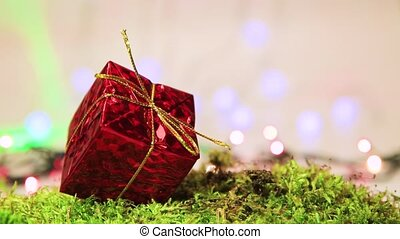 Red gift on green moss, Christmas tree decoration with bokeh back.