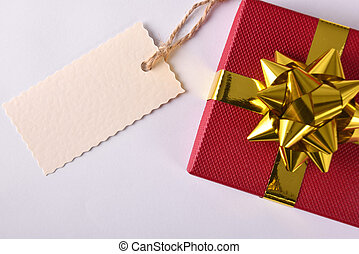 Red gift with golden ribbon and label on the left