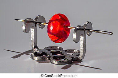 Red glass bead on the needle on grey background