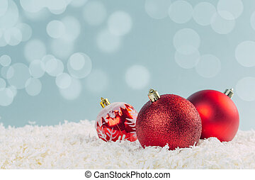 red glass Christmas balls in the snow on a blue background with bokeh lights. happy new year card