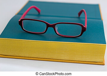 Red glasses and gold book
