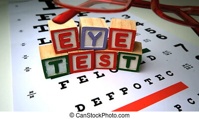 Red glasses falling next to blocks spelling out eye test in...