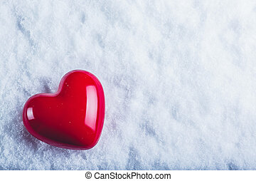 Red glossy heart on a frosty white snow background. Love and...